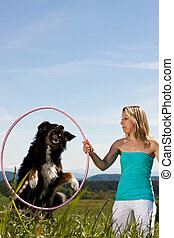 Blonde woman holding hula hoop and dog jumps through