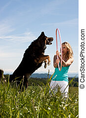 young blond woman holding hula hoop and dog jumps through