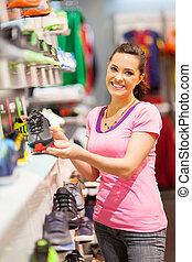 woman choosing sports shoes - happy young woman choosing...