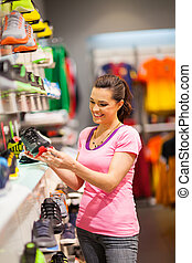 woman shopping for sports shoes - happy young woman shopping...