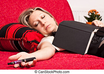 Blond woman asleep with E-Cigarette - Young blonde woman...