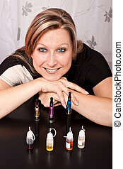 Woman shows her collection of e-cigarettes and various...