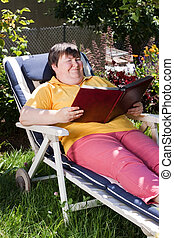 disabled woman reading a book in the garden