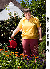 disabled woman with a pot pours flowers - mentally disabled...