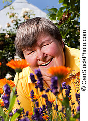 disabled woman lying on grass and smell on flowers -...