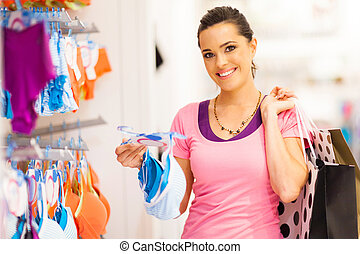 young woman shopping for lingerie in clothing store