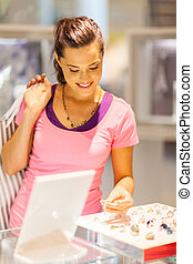 young woman choosing jewellery in shop