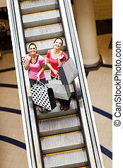 shopping women on escalator - happy shopping women on...