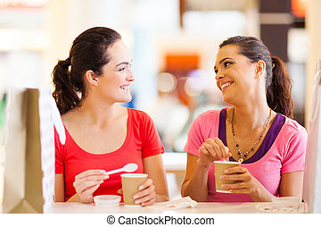 friends having drinks in cafe - two happy friends having...