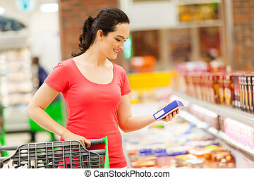 grocery shopping in supermarket - young woman doing grocery...