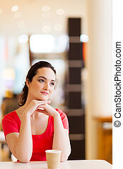 young woman sitting in coffee shop - happy young woman...