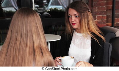 girls talking in a cafe