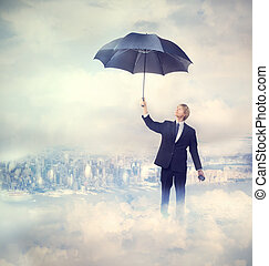 Business man holding an umbrella on the clouds