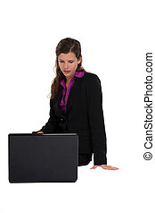 woman in a suit looking at her laptop