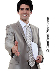young businessman all smiles shaking hands with invisible...