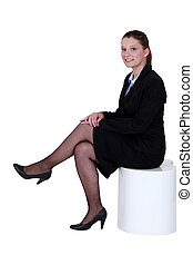 Young woman in smart suit sitting on a stool