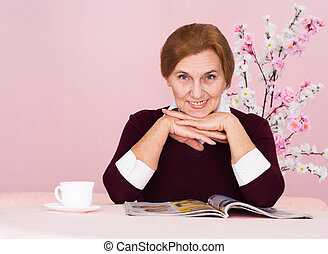 Nice Caucasian aged woman sitting with a magazine on a pink...