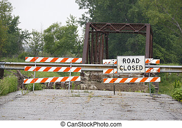 Road Closed - Road closed sign on a rural road with a bridge...