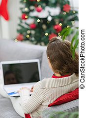 Woman using laptop near Christmas tree Rear view