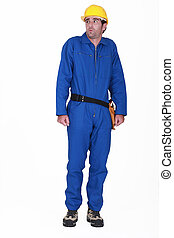tradesman in blue jumpsuit being scolded