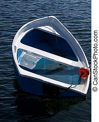 sinking boat - small blue plastic boat sinking after storm