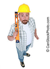 Surprised builder holding spirit-level