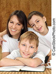 Joy charming mom and sons sitting on a brown background