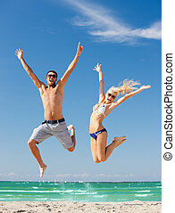 happy couple jumping on the beach - picture of happy couple...