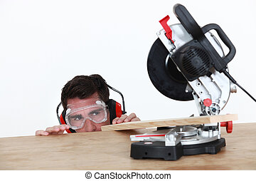 craftsman cutting a wooden board with an electric saw