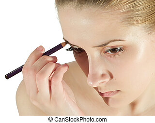 make up - A young woman putting make up on her face with a...