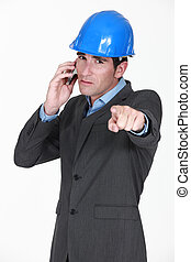 foreman on the phone pointing at something