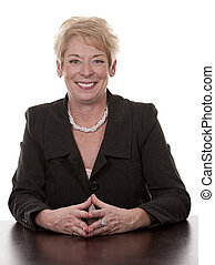 business woman - mature woman sitting behind desk on white...