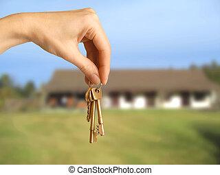 housekeys - female hand holding house keys in front of...