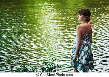 Girl staying by a lake