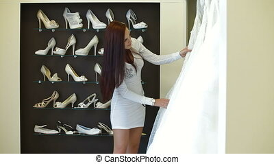 Bride Choosing Wedding Dress - Young attractive woman...