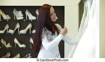 Bridal Shop - Young attractive woman choosing wedding dress...