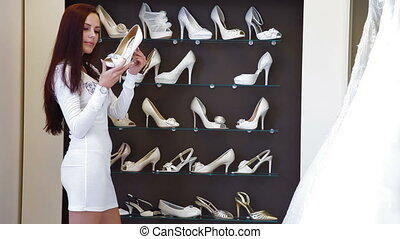 Choosing Wedding Shoes - Young attractive woman choosing...