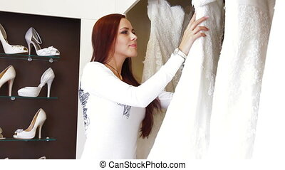 Bridal Boutique - Young attractive woman choosing wedding...