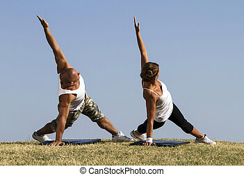 Couple doing yoga in nature Beautiful blue skies in...