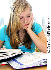 Teenage girl studying with textbooks