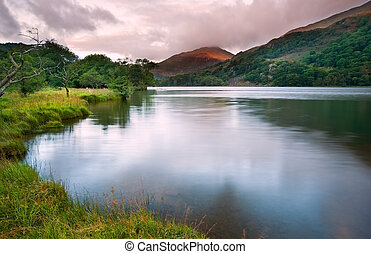 View of sunrise over Llyn Gwynant towards landscape of Yr Afan mountain in Snowdonia National Park