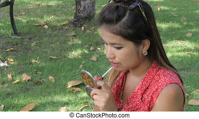 Asian Girl Applies Lip Gloss - A pretty Thai girl applies...