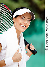 Successful female tennis player with towel on her shoulders....