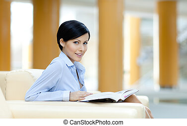Business woman sits at the sofa with book - Business woman...