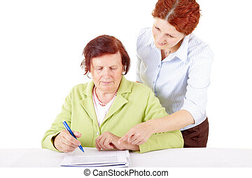 signature - young woman helping senior woman to write a...