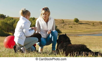Feeding their Newfoundland Dogs - Mother and Daughter...