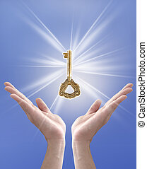 the key to success (hand holding key against blue sky)