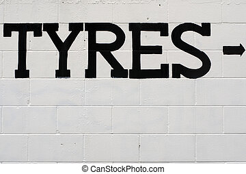 Tyres wording painted on a white and blue brick wall with...