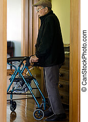 Elderly man use a walker (walking frame) - An old disabled...
