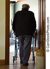 Elderly man use a walker walking frame - An old disabled...
